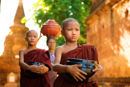 Young Buddhist monks walking morning alms in Old Bagan, Myanmar photo