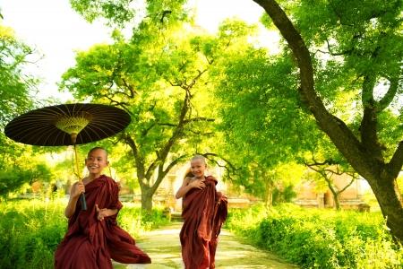 ミャンマー修道院、外の緑の木の木陰の下で屋外を実行する 2 つの少しの仏教の僧侶。