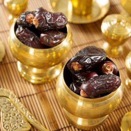 frutos secos: Fecha de frutas secas de palma o kurma, alimentos ramadan que comen en el mes de ayuno. Pila de frescas frutas secas de la fecha en recipiente de metal dorado.