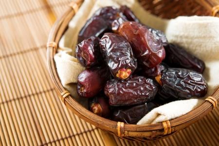 Gedroogde dadelpalm vruchten of kurma, ramadan voedsel dat gegeten in vastenmaand. Stapel van verse gedroogde vruchten datum in bamboe mandje. Stockfoto