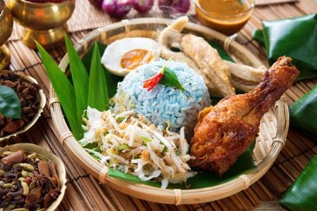 Kerabu Nasi o ulam nasi, plato de arroz malayo popular. El color azul de arroz resultante de los pétalos de las flores de mariposa-pea. Comida malaya tradicional, la cocina asiática. Foto de archivo