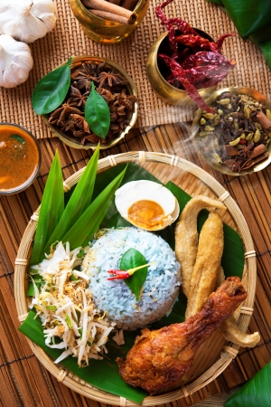 Traditional Malaysian food, Asian cuisine. Nasi kerabu is a type of nasi ulam, popular Malay rice dish. Blue color of rice resulting from the petals of  butterfly-pea flowers photo