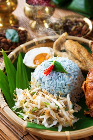 Nasi kerabu is a type of nasi ulam, popular delicious Malay rice dish. Blue color of rice resulting from the petals of  butterfly-pea flowers. Traditional Malaysian food, Asian cuisine. photo