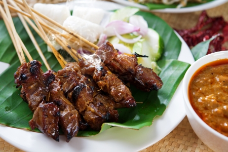 satay sauce: Satay or sate, skewered and grilled meat, served with peanut sauce, cucumber and ketupat. Traditional Malay food. Delicious hot and spicy Malaysian dish, Asian cuisine.