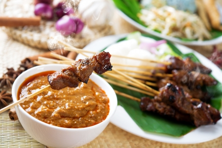 Satay or sate, skewered and grilled meat, served with peanut sauce, cucumber and ketupat. Traditional Malay food. Malaysian dish, Asian cuisine. Stock Photo