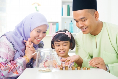 Islamic banking concept. Southeast Asian family counting money at home. Little Malay girl and parents saving money. Muslim father, mother and daughter living lifestyle. Stock Photo