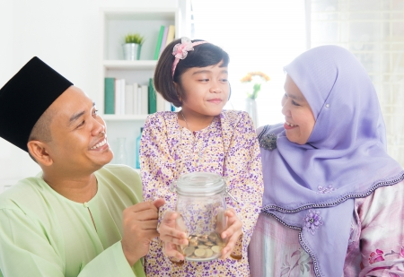 Islamic banking concept. Southeast Asian Malay family saving money at home. Muslim father, mother and daughter living lifestyle. photo