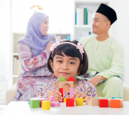 Malay girl building a wooden toy house. Southeast Asian family at home. Muslim parents and child living lifestyle. photo