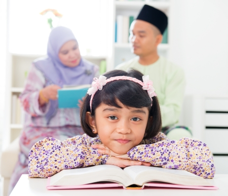 Muslim girl reading book. Malay family at home. Southeast Asian parents and child living lifestyle. photo