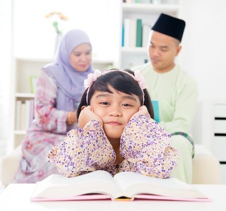 petite fille musulmane: Malay fille lisant le livre. Famille sud-est asiatique � la maison. Les parents musulmans et style de vie de vie de l'enfant.