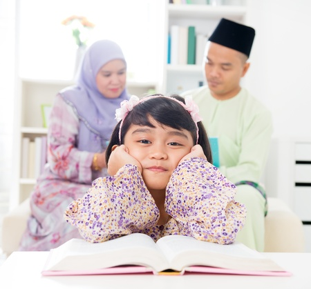 Malay girl reading book. Southeast Asian family at home. Muslim parents and child living lifestyle. photo