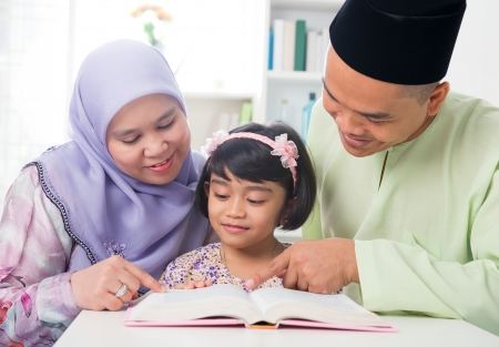 Malay Muslim parents teaching child reading a book. Southeast Asian family at home.  Stock Photo