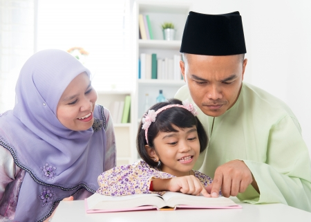 quran: Malay Muslim parents teaching child reading a book. Southeast Asian family at home.  Stock Photo