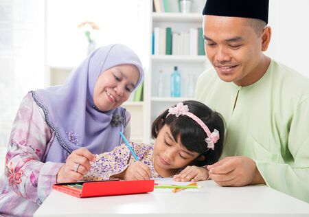Muslim family drawing and painting picture at home. Southeast Asian family lifestyle. Happy smiling parents and child. photo