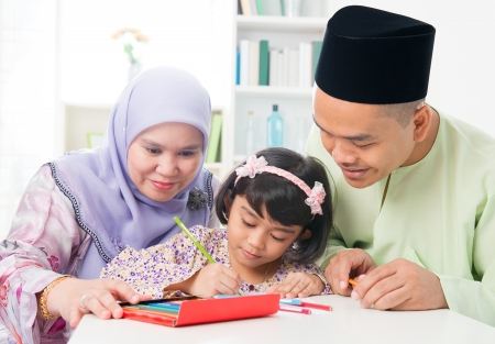 Southeast Asian family drawing and painting picture at home. Muslim family lifestyle. Happy smiling parents and child. photo