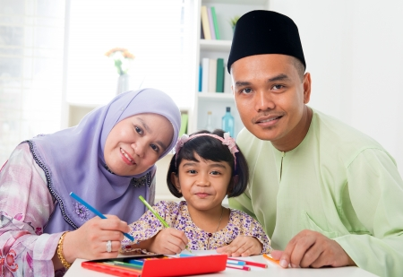 Southeast Asian family drawing and painting picture at home. Malay Muslim family lifestyle. Happy smiling parents and child. photo