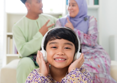Muslim girl listening to song at home. Southeast Asian family living lifestyle. Happy smiling Malay parents and child. Stock Photo - 20434459