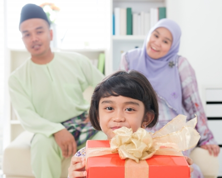muslim celebration: Southeast Asian girl with gift box. Muslim family living lifestyle. Happy smiling Malay parents and child. Stock Photo