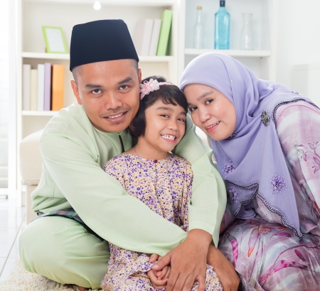 southeast: Muslim parents hugging child. Southeast Asian Malay family lifestyle. Happy smiling father mother and daughter.