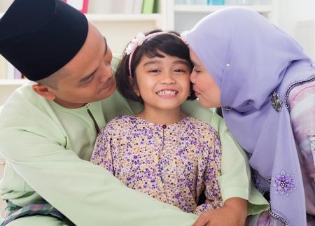 イスラム教徒の両親は子供にキスします。東南アジアのマレー語家族のライフ スタイル。幸せな父の母と娘笑顔します。 写真素材