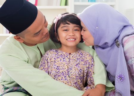 Muslim parents kissing child. Southeast Asian Malay family lifestyle. Happy smiling father mother and daughter.