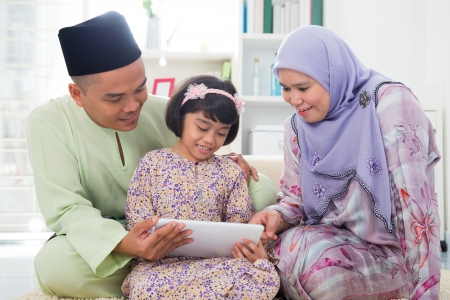 family living: Southeast Asian family using tablet pc computer at home. Muslim family living lifestyle. Happy smiling Malay parents and child.