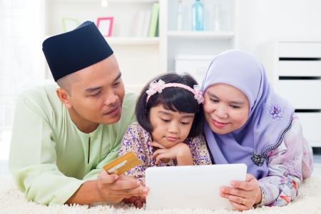 Southeast Asian family using tablet pc computer online shopping with credit card at home. Muslim family living lifestyle. Happy smiling Malay parents and child. photo