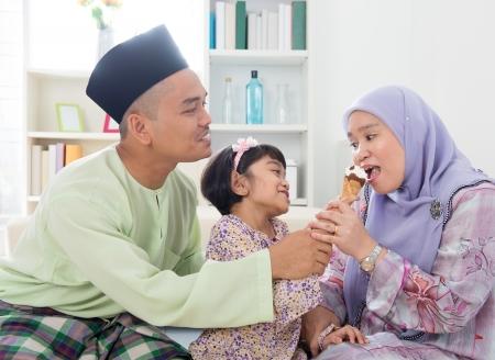 malay food: Feeding ice cream. Muslim girl feeding mother an ice cream. Beautiful Southeast Asian family living lifestyle at home.
