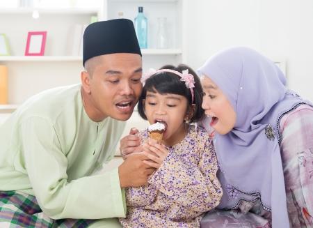 familia comiendo: Comer helado. Familia musulmana compartiendo un helado. Hermosa Sudeste Asiático familiares modo de vivir en el país. Foto de archivo