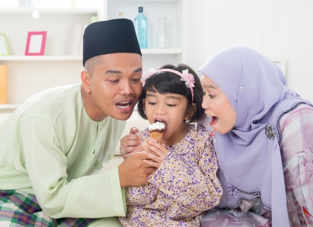 malay food: Eating ice cream. Muslim family sharing an ice cream. Beautiful Southeast Asian family living lifestyle at home.
