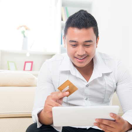 shopping man: Internet shopping man online with tablet pc and credit card. Internet shopper buying things on the internet. Handsome multicultural Asian model. model happy Stock Photo