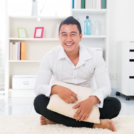 hombre sentado: Hombre asi�tico joven que sonr�e feliz. Lifestyle Southeast Asia hombre en casa. Modelo masculino asi�tico hermoso.