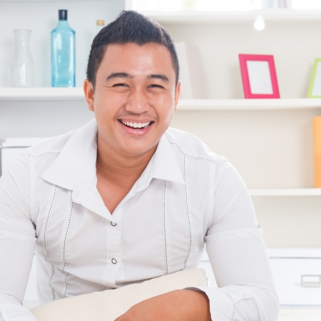malay boy: Good looking young Asian man smiling happy. Lifestyle Southeast Asian man at home. Handsome Asian male model. Stock Photo