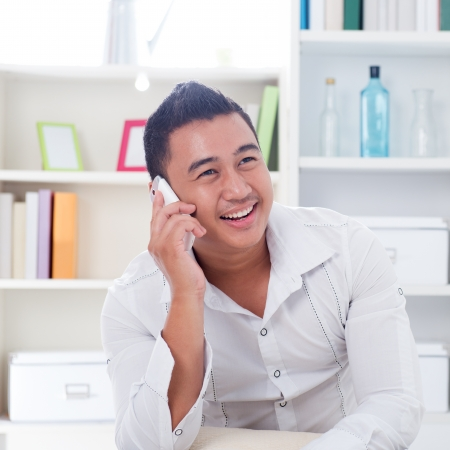 Young Asian man talking on the phone. Lifestyle Southeast Asian man at home. Handsome Asian male model. photo