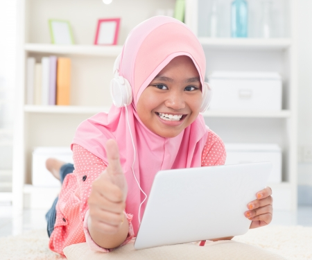 Asian teen listening to music with headphone and thumb up. Southeast Asian teenager at home. Muslim teenage girl living lifestyle. Stock Photo - 20434455