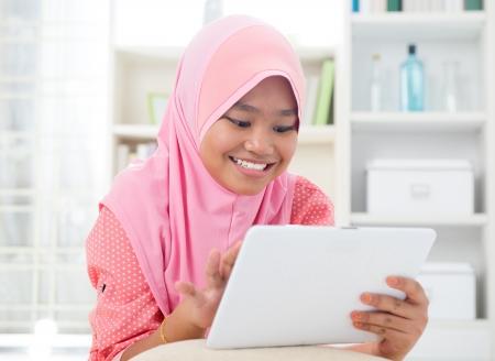 fille arabe: Adolescent asiatiques utilisant un ordinateur Tablet PC. Adolescent Sud-Est asiatique à la maison. Musulman adolescent style de vie de vie de jeune fille. Banque d'images