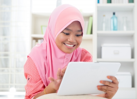 Asian teen using tablet pc computer. Southeast Asian teenager at home. Muslim teenage girl living lifestyle. photo