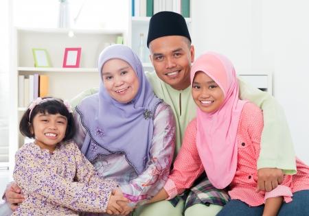幸せなアジア家族の自宅で。イスラム教徒の家族は屋内で楽しい時を過します。東南アジアの親と子供たち笑みを浮かべてします。 写真素材