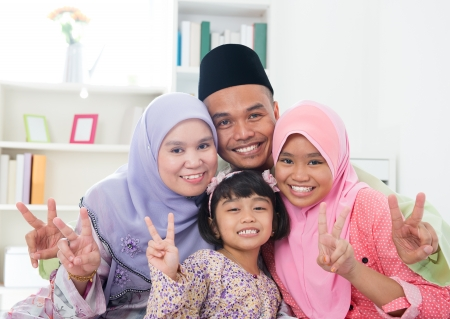 traditional: Happy Asian family at home. Muslim family showing v victory hand sign and having fun. Southeast Asian parents and children smiling.