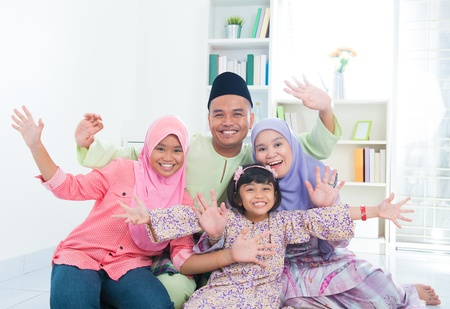 Happy Asian family at home. Muslim family having fun. Southeast Asian parents and children open arms smiling. photo