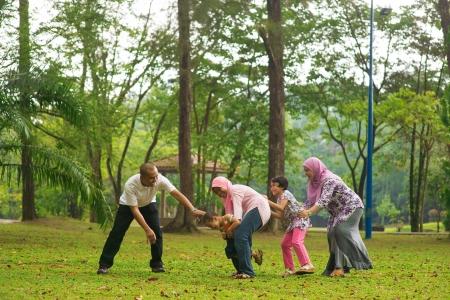 familias unidas: Familia musulmana que se divierten en parque verde al aire libre. Hermosa familia del sudeste asiático jugando juntos.