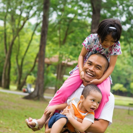 malay boy: Southeast Asian family having fun at green outdoor park. Beautiful Muslim family playing together. Stock Photo