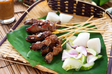 satay sauce: Satay or sate, skewered and grilled meat, served with peanut sauce, cucumber and ketupat, Malaysia or Indonesia food. Traditional Malay food. Hot and spicy Malaysian dish, Asian cuisine.