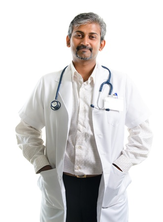 Mature Indian male medical doctor standing isolated on white background photo