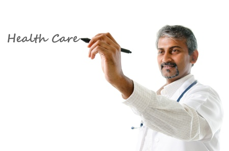 india people: Health care concept. Mature Indian male medical doctor writing on blank space, standing isolated on white background. Handsome Indian model portrait.