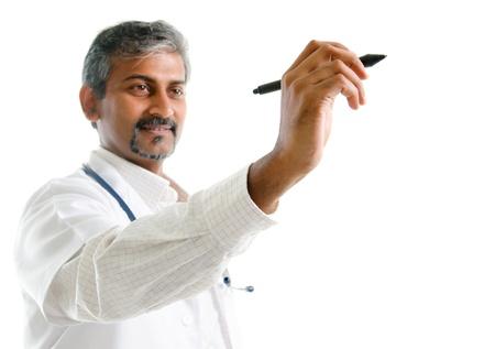 Indien d'âge mûr médecin de sexe masculin dessin ou dessiner sur un espace vide, debout isolé sur fond blanc