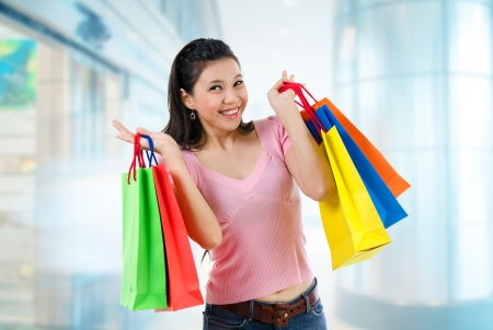 Happy Asian shopping woman smiling holding many shopping bags at the mall photo