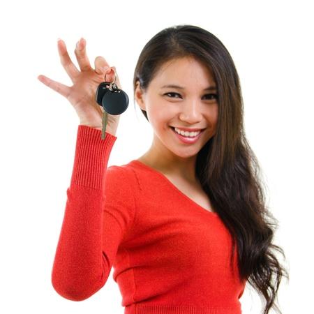 Jonge vrouw die haar eerste eigen auto sleutel geïsoleerd op witte achtergrond