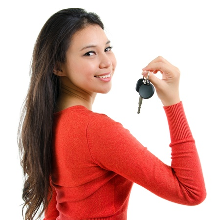 southeast: Attractive young woman holding her first own car key isolated on white background Stock Photo