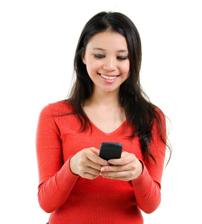 Young Woman smiling and texting on her mobile phone, isolated over white background photo